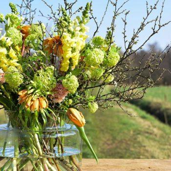 Glazen vaas met boeket bloemen